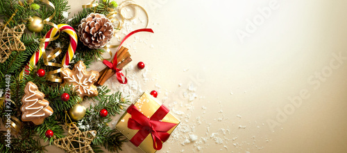 Christmas decoration composition on light gold background with beautiful Golden gift box with red ribbon, fir branches, cones, stars, Christmas cookies,cinnamon, top view, copy space, banner format.
