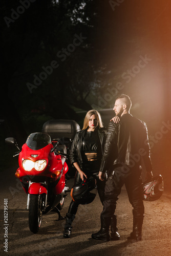 man and woman bikers in leather jackets with sports motor bike on the road in the evening