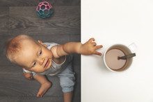 Child Burn And Scald Injury Concept - Little Boy Reaching For Hot Drink Mug On The Table
