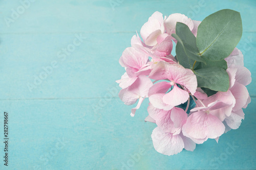 Deurstickers Hydrangea Pink hydrangea flower with a branch of eucalyptus leaves in a vase on a blue wooden table, copy space, top view.