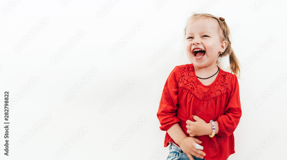 Fototapeta Cheerful laughing little girl in red blouse . Studio Shooting on the white background.