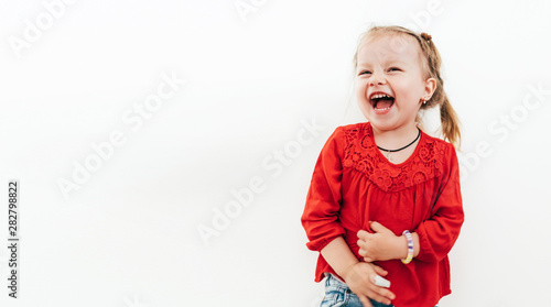 Obraz Cheerful laughing little girl in red blouse . Studio Shooting on the white background. - fototapety do salonu