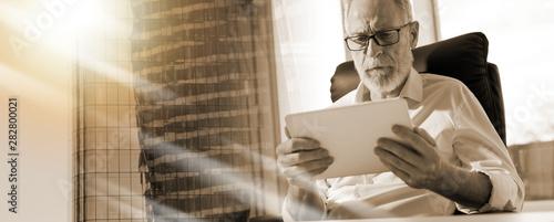 Senior businessman using a digital tablet, hard light; multiple exposure