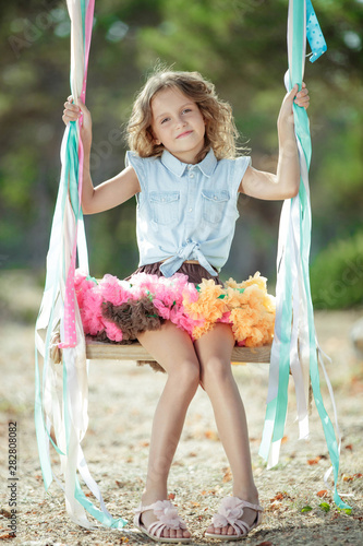 Little girl riding on a swing.