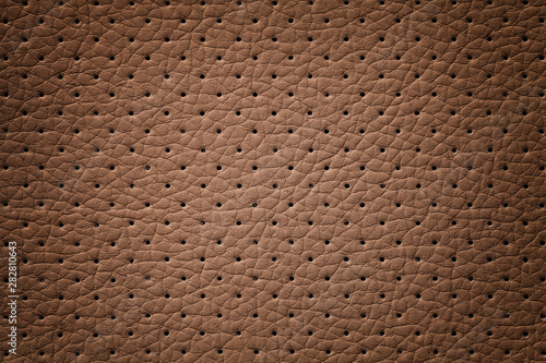 Valokuva  Perforated brown leather texture background, closeup