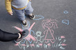 Children's drawing with chalk on the asphalt, family with no dad. Son and mother crossed out father. Family divorce.