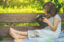 Reading The Holy Bible In Outdoors. Christian Girl Holds Bible In Her Hands Sitting On A Bench. Concept For Faith, Spirituality And Religion. Peace, Hope