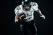 Leinwanddruck Bild - American football sportsman player in helmet isolated run in action on black background. Sport and motivation wallpaper.