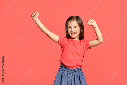 Close-up studio shot of beautiful brunette little girl posing against a pink background.
