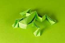 Green Origami Frog On Green Background. Japanese Art Of Paper Folding. Flat Square Sheet Of Paper Transferred Into A Finished Sculpture Through Folding And Sculpting. Close Up. Macro Photo.
