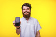 canvas print picture - Photo of happy bearded man showing his smartphone and looking at the camera
