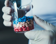Doctor`s Hand Holding Laboratory Glass Test Tube Filled With Colorful Pills.