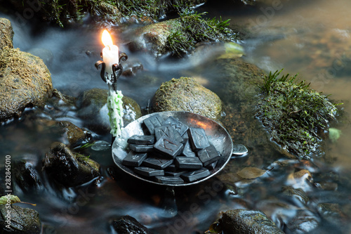Photo  Norse Runes in a forged bowl with candle