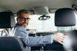 canvas print picture - senior businessman driving car looking at camera