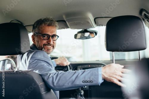 senior businessman driving car looking at camera Canvas Print