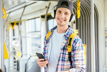Young Man Is Standing In A Bus With Headset On His Head And Listening To The Music.