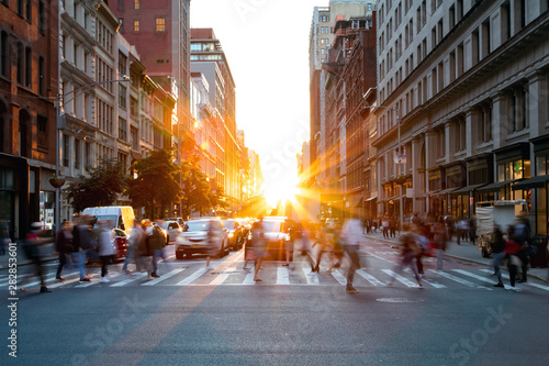 Crowds of busy people walking through the intersection of 5th Avenue and 23rd Street in Manhattan, New York City