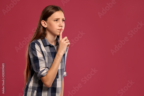 Fotografie, Obraz  Beautiful teenage girl in a casual checkered shirt is posing against a pink studio background