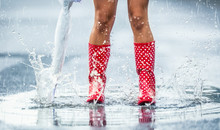 Woman Legs In Dotted Red Rubber Boots With Umbrella Jumping In The Summer Spring Or Autumn Puddles