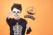 Leinwanddruck Bild Trick or treat.Funny child in a skeleton costume with halloween pumpkin