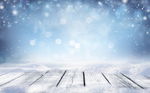 Beautiful Winter Snowy Blurred Defocused Blue Background And Empty Wooden Flooring. Flakes Of Snow Fall And Sparkle On Light, Copy Space.