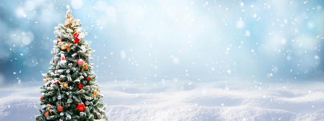 Beautiful Festive Christmas snowy background. Christmas tree decorated with red balls and knitted toys in forest in snowdrifts in snowfall outdoors, banner format, copy space.