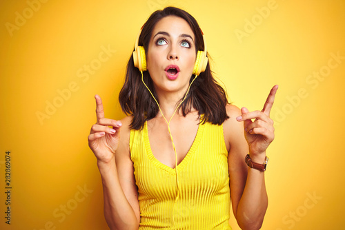 Young beautiful woman listening to music using headphones over yellow isolated background amazed and surprised looking up and pointing with fingers and raised arms. - 282869074