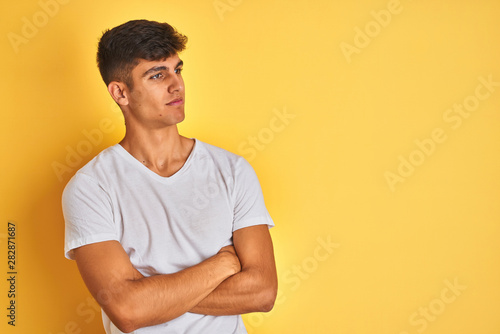 Foto  Young indian man wearing white t-shirt standing over isolated yellow background