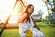 A Portrait Of Trisomie 21 Adult Girl Outside At Sunset Having Fun On A Park
