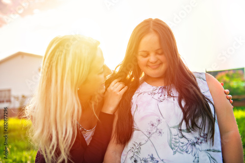 A Portrait of trisomie 21 adult girl smilin outside at sunset with family friend Canvas Print