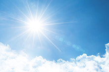 Clear Sky With Bright Sun And Rays In The Atmosphere, Below Are Light Fluffy Clouds.