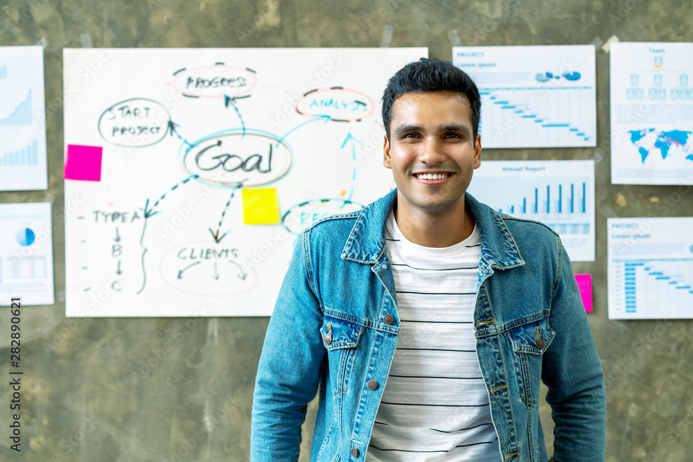 Fototapeta Portrait of Happy indian man in jeans jacket standing in creative office workplace with document plan on wall background. Headshot of smiling freelancer leaning on table with feeling confident.
