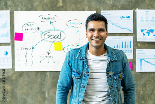 Fototapeta Portrait of Happy indian man in jeans jacket standing in creative office workplace with document plan on wall background. Headshot of smiling freelancer leaning on table with feeling confident. obraz