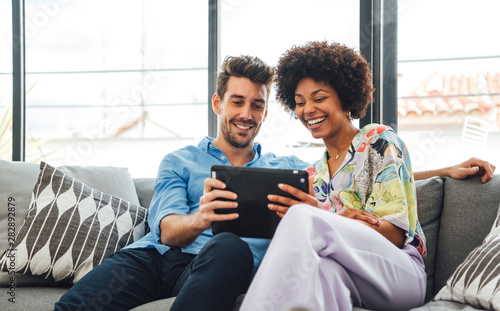 Foto  Excited diverse couple using tablet on couch