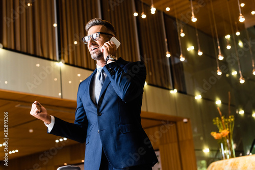 Photo sur Toile Les Textures handsome businessman in suit and glasses talking on smartphone