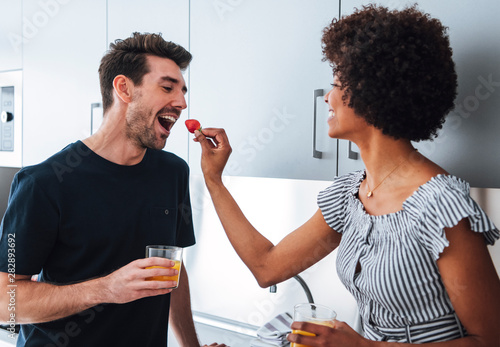 Stampa su Tela  Tender interracial couple feeding each other with berries