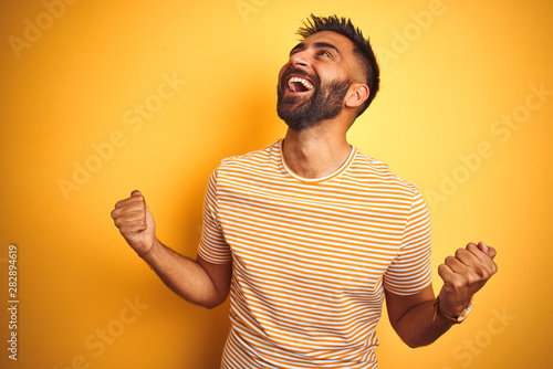 Young indian man wearing t-shirt standing over isolated yellow background celebrating surprised and amazed for success with arms raised and eyes closed Fototapet