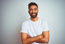 Young Indian Man Wearing T-shirt Standing Over Isolated White Background Happy Face Smiling With Crossed Arms Looking At The Camera. Positive Person.