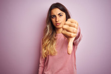 Young Beautiful Woman Wearing A Sweater Over Pink Isolated Background Looking Unhappy And Angry Showing Rejection And Negative With Thumbs Down Gesture. Bad Expression.