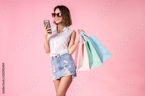 Foto  Asian pretty young woman walking over pink  pastel background