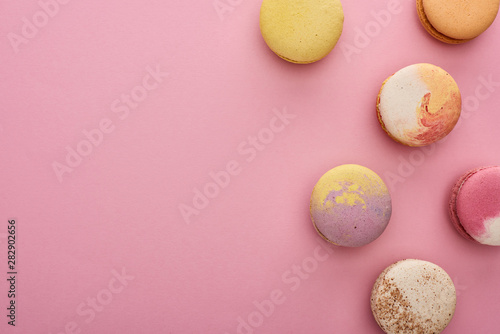 Poster Macarons top view of multicolored delicious French macaroons on pink background
