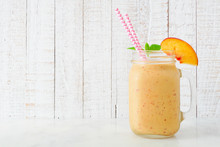 Peach Smoothie In A Mason Jar Glass With Paper Straws.  Side View With A White Wood Background.