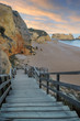 Evening landscape. staircase descends to a beach with rocks on the shore of the Atlantic Ocean at sunset in the vicinity of the city of Lagos in Portugal