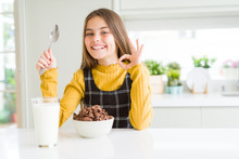 Beautiful Young Girl Kid Eating Chocolate Cereals And Glass Of Milk For Breakfast Doing Ok Sign With Fingers, Excellent Symbol