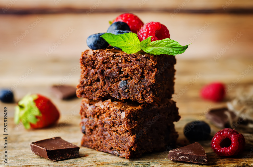 Fototapeta Chocolate brownie with berries and mint leaves
