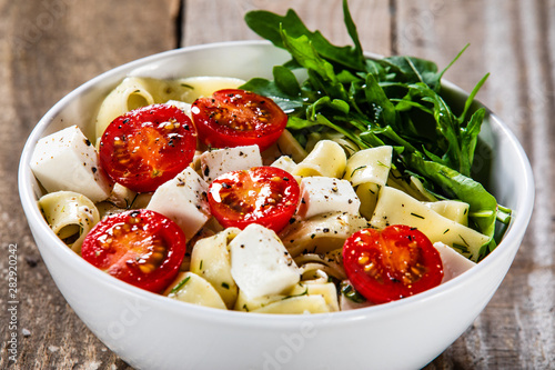 Pasta with tomatoes and white cheese on wooden table