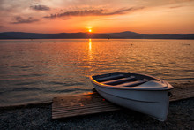 Boat On The Lake Against The Backdrop Of A Picturesque Sunset