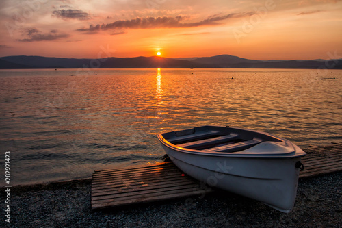 Wallpaper Mural Boat on the lake against the backdrop of a picturesque sunset