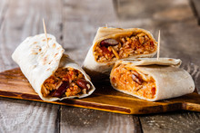 Burritos On Cutting Board On Wooden Table