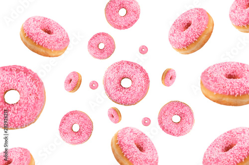 Fotografía Falling or flying pink glazed doughnuts with sprinkles in motion isolated on white background